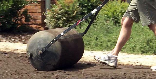 Мужчина прокатывает почву катком после посева газона на даче