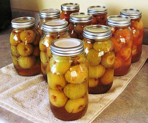 Заготовки из яблок. Яблочный компот в банках на столе